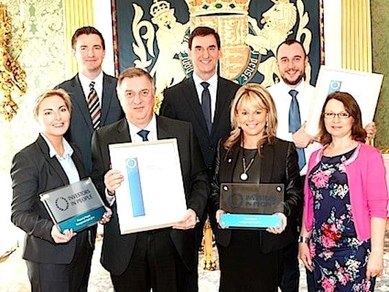 Sandra Corkin, Managing Director, and staff team members, display Oasis Travel's Investors in People awards
