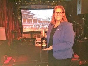 Commissioner Kristen Branscum presented quiz winners Deirdre Grant, Joe Walsh Tours, and Cian Scanlon, JustSplit.com, with a bottle of Kentucky bourbon each